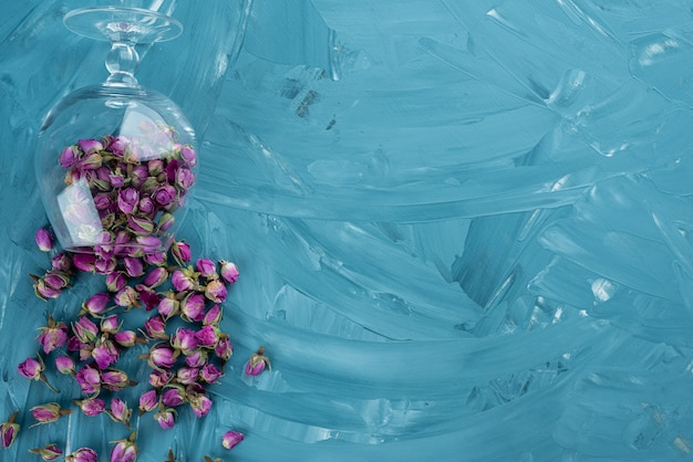 Glass of dried purple roses scattered on blue background.