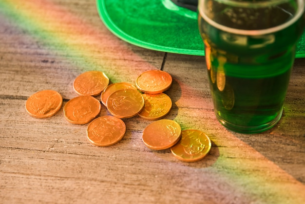 Glass of drink near heap of coins and saint patricks hat at table