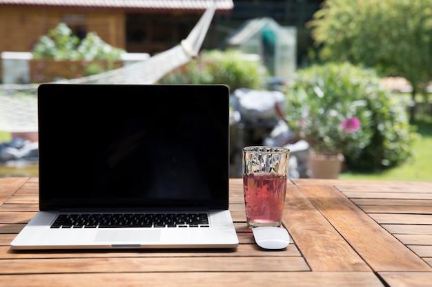 Glass of drink near laptop in garden