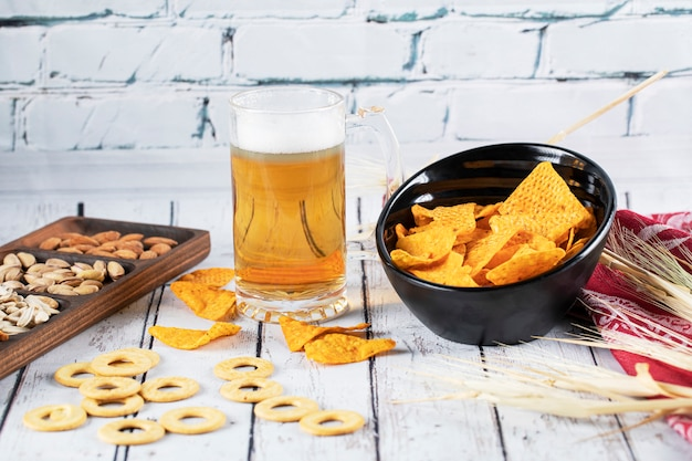 A glass of drink served with snacks