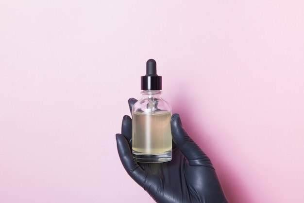 Glass dropper bottle in a black medical female hand on a pink surface