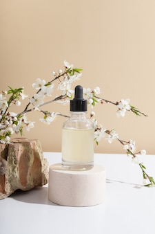 A glass dropper bottle on a podium with blooming twigs on a biege background
