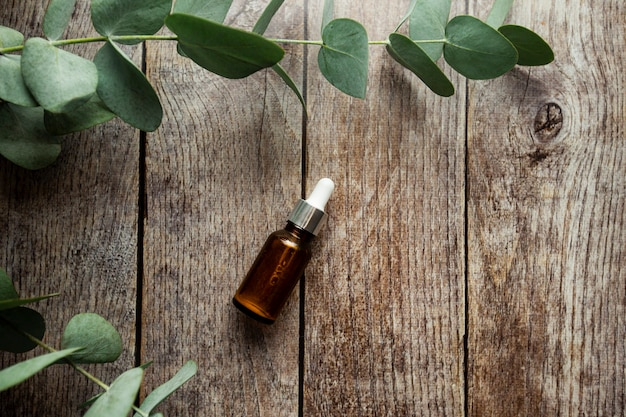 Стеклянная бутылка-капельница с бутылкой-пипеткой с прозрачной гиалуроновой косметической сывороткой и концепцией ухода за кожей на деревянном фоне с зелеными листьями и веточкой эвкалипта