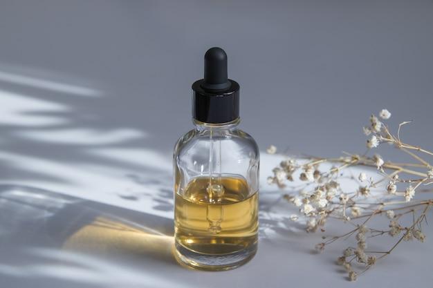 Стеклянная бутылка-капельница с косметикой для ухода за кожей возле гипсофилы
