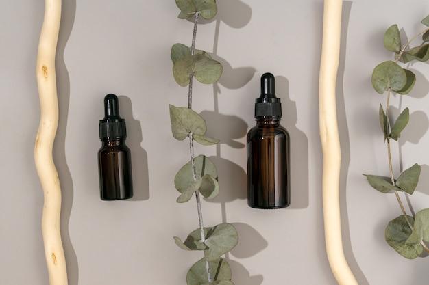 ユーカリオイル入りのガラススポイトボトル。トレンディなオーガニック化粧品、フェイシャルアンチエイジングオイル。木の棒で灰色の背景にユーカリの葉のある静物画。