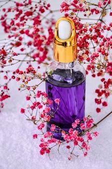 Стеклянная капельница косметического масла и сушеных цветов и трав на белом натуральное травяное масло для ухода за кожей