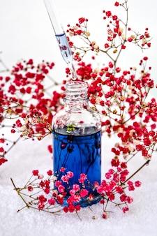 Стеклянная пипетка косметического масла и цветов и трав на белом натуральное органическое травяное масло для ухода за кожей