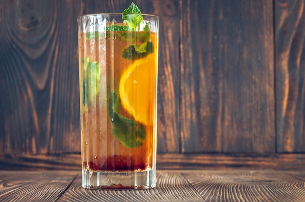 Glass of dutch orange cup cocktail garnished with orange slice and fresh mint leaves