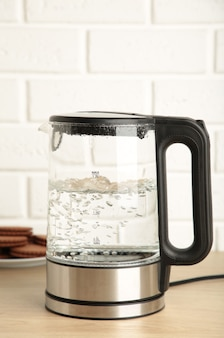 Glass electric kettle with boiling water and chocolate chip cookie on white background. top view.