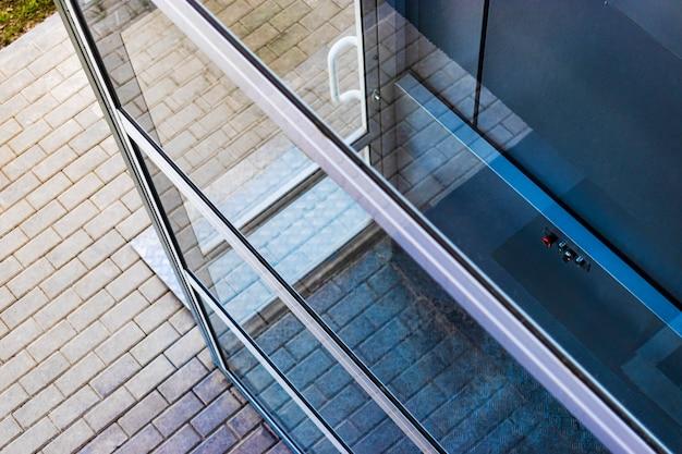 近代的な建物の入り口にある障害者と障害者のためのガラス張りのエレベーター。人の世話。