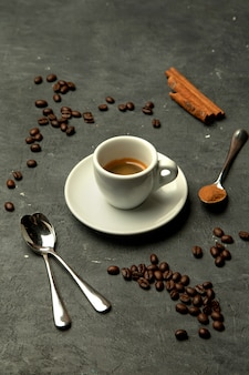 Glass of espresso coffee in grey background decorated with coffee beans