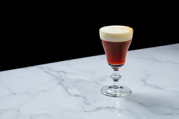 Glass of espresso martini cocktail on marble table with copy space for text