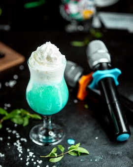 A glass of exotic cocktail garnished with whipped cream in karaoke club