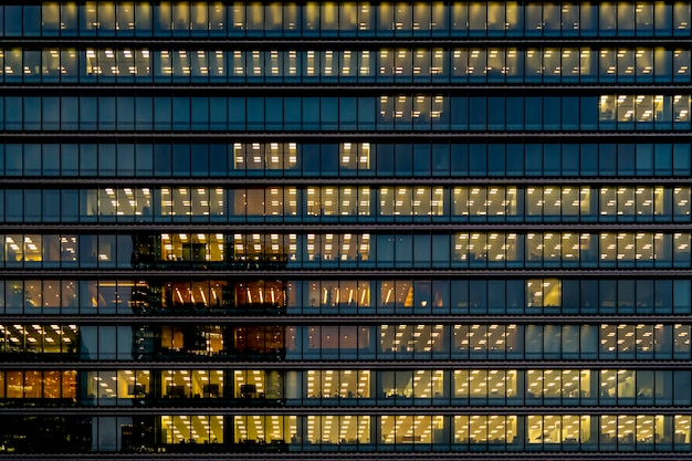 Glass exterior facade with interior yellow lighting glow in each floor in a skycraper
