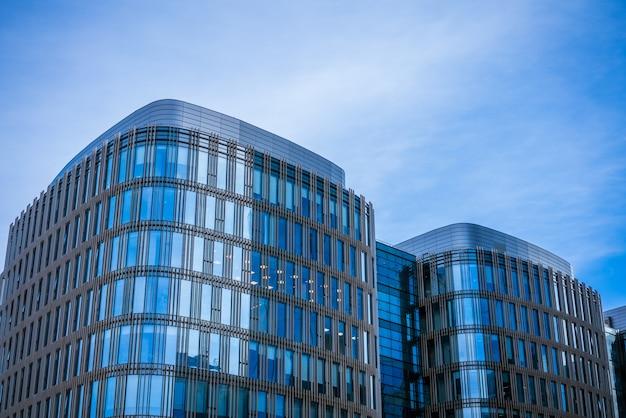 青い空を背景にオフィスビルのガラスのファサード