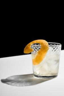 Vetro riempito con cocktail di bevanda alcolica e scorza di limone