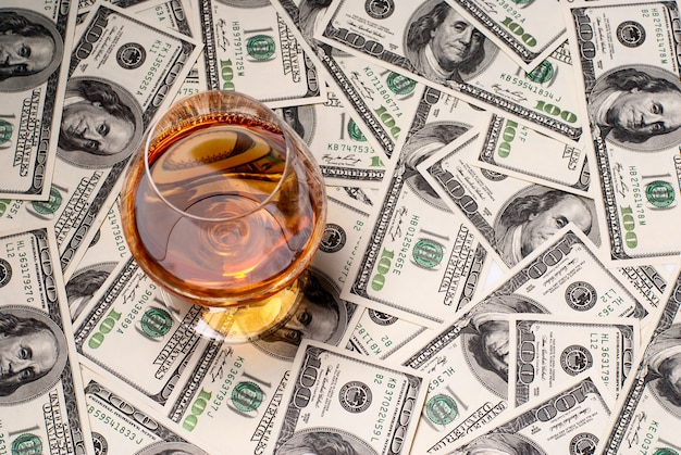 A glass filled with brandy and u.s.dollars. studio shot.