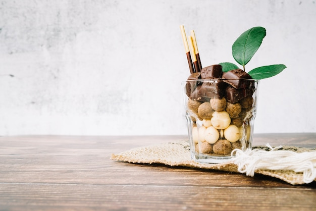 Glass filled with chocolates candies and stick on wooden table
