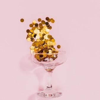 金色の紙吹雪で満たされたガラス
