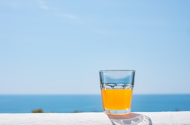 A glass filled with juice against the backdrop of the sea.