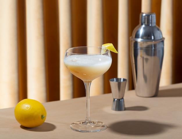 Стакан, наполненный кислым коктейлем виски с лимоном и шейкер на столе