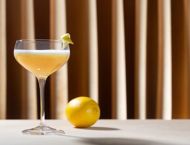 テーブルの上にレモンとウイスキーサワーカクテルを詰めたグラス