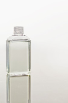 Glass flask on a mirror against white background