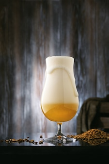 Glass of foaming beer with barley malt on vintage wooden board