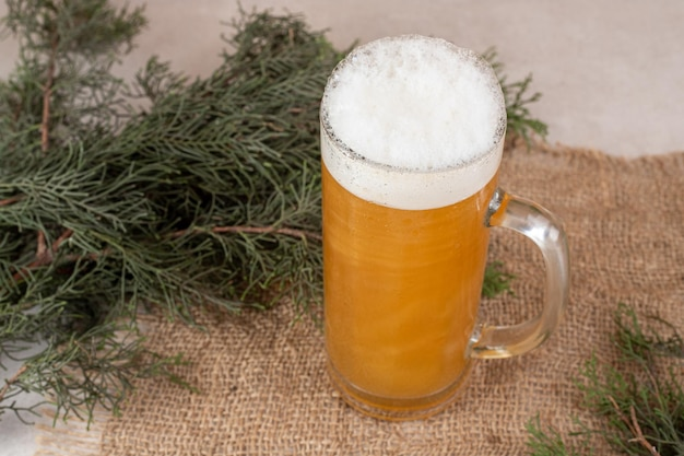 Glass of foamy beer on burlap with pine branch.
