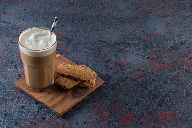 Glass of foamy cold coffee with biscuits on wooden plate.