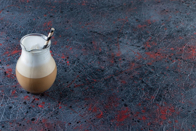 Glass of foamy cold coffee with straw on marble surface. Free Photo