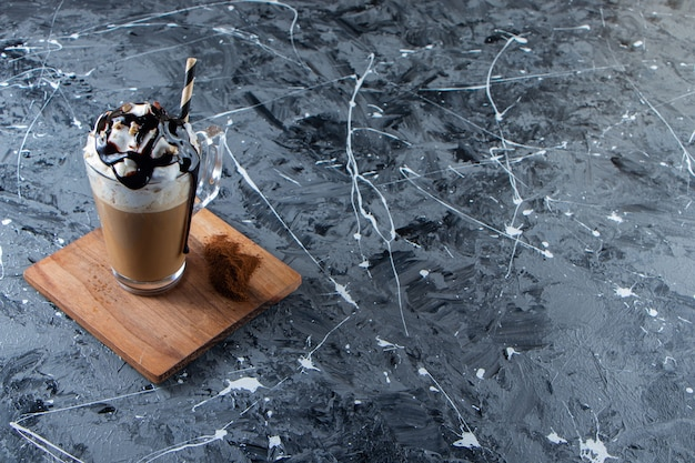 Glass of foamy cold coffee with whipped cream and chocolate on wooden plate.