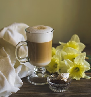 A glass of foamy latte decorated with daffodil