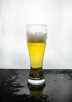 Glass of foamy light beer with contrasting light , with reflection and drops