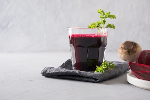 Glass of fresh beetroot juice garnish parsley on grey.