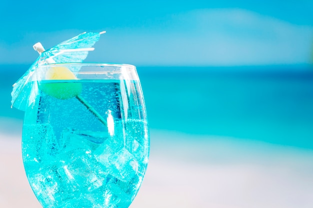 Glass of fresh blue drink decorated with olive and umbrella