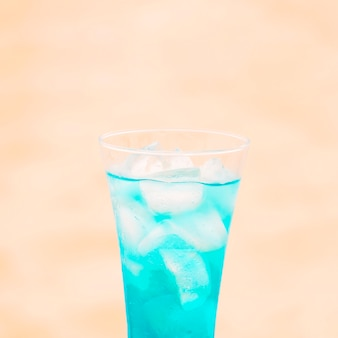 Glass of fresh blue drink with ice cubes