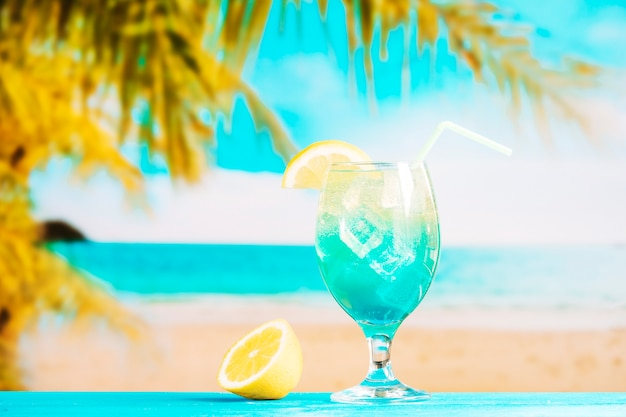 Glass of fresh blue drink with straw and sliced lime