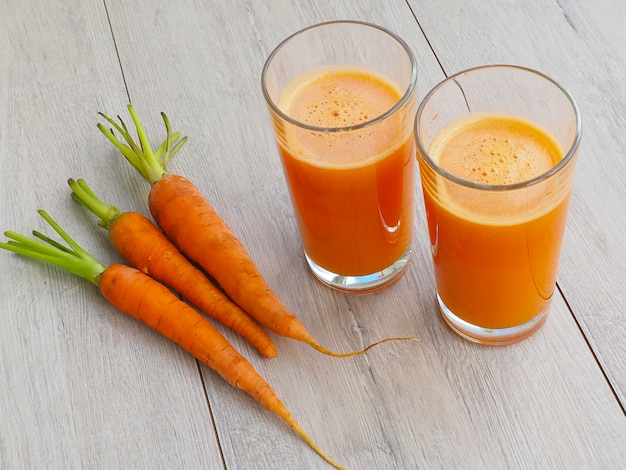 Glass of fresh carrot juice with vegetables on wood background.