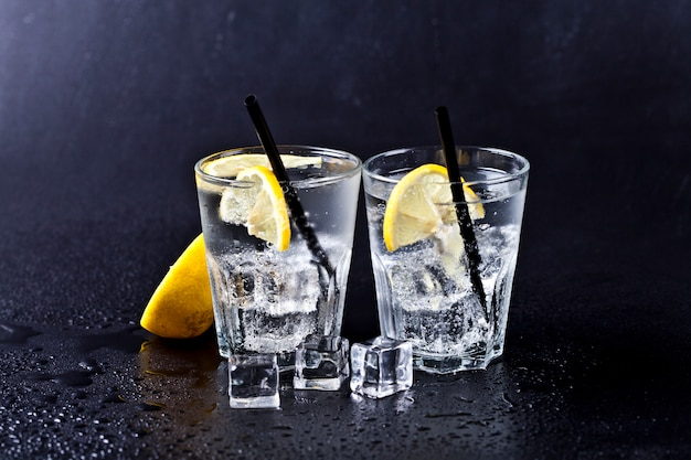 Glass of fresh cold carbonated water with ice cubes and lemon slices