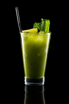 Glass of fresh cold smoothies with straw isolated on black