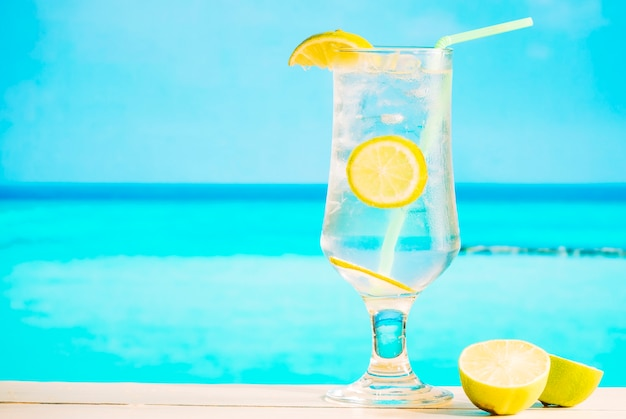 Glass of fresh lemon drink with straw and sliced lime