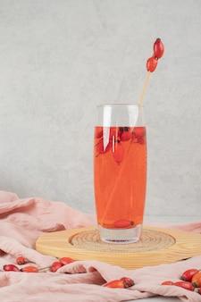 Bicchiere di limonata fresca con cinorrodi sul piatto di legno.