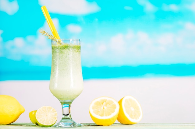 Glass of fresh lime smoothie and sliced citrus