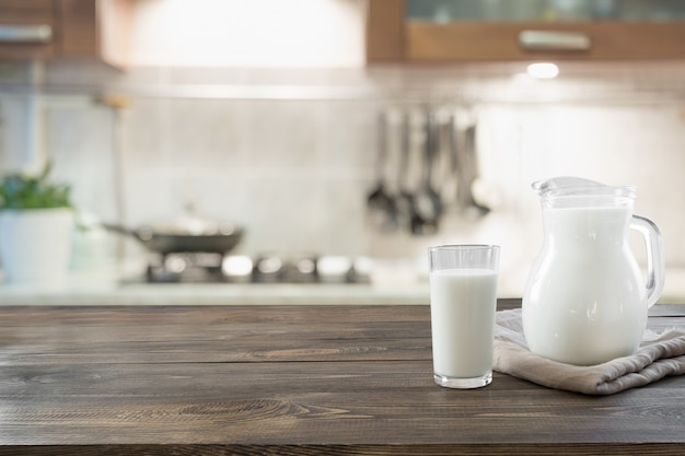 Glass of fresh milk and jug on wooden tabletop with blur kitchen as background.