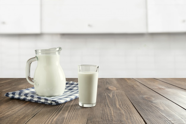 Glass of fresh milk and jug on wooden tabletop with blured white kitchen as background.