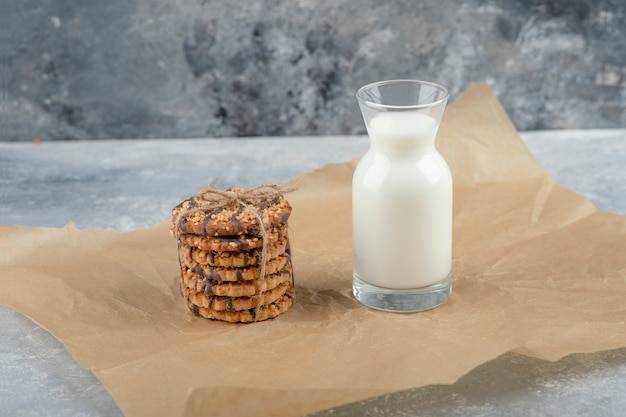 Glass of fresh milk and stack of delicious biscuits on paper sheet.