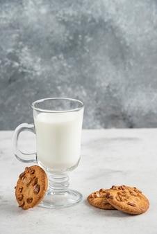 Bicchiere di latte fresco e gustosi biscotti sul tavolo di marmo.