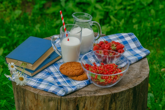 Glass of fresh milk with fresh raspberries ripe for breakfast on a wooden surface