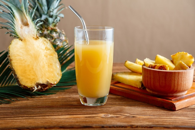 Glass of fresh natural pineapple juice with metal reusable tube on brown wooden table